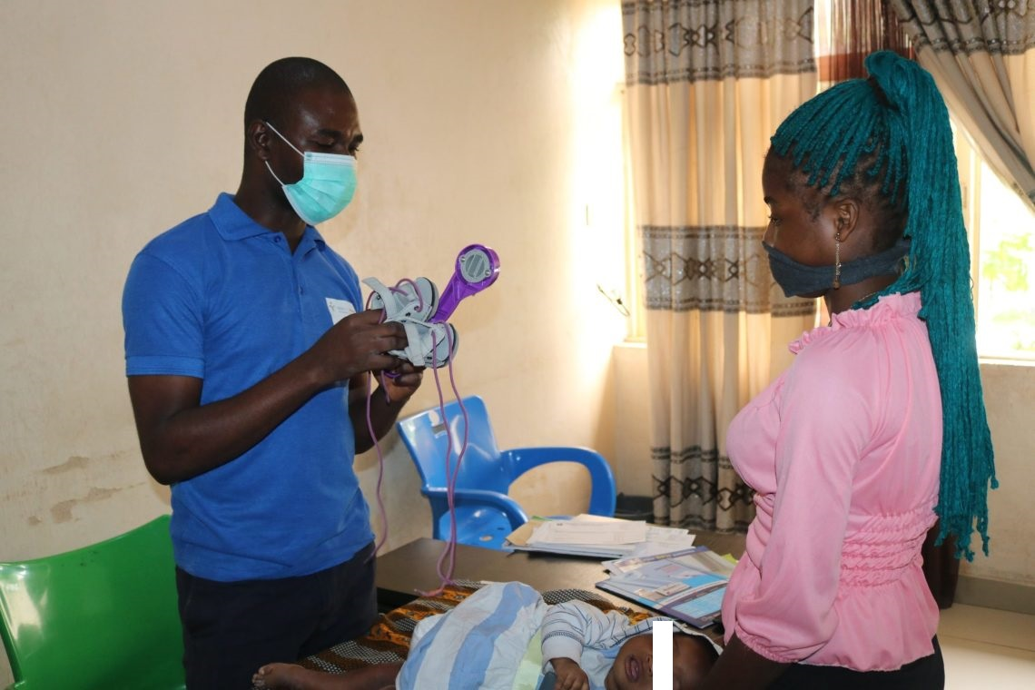 Tochukwu Ekwueme, a clubfoot clinic assistant at FMC explains what a brace is to a mother.