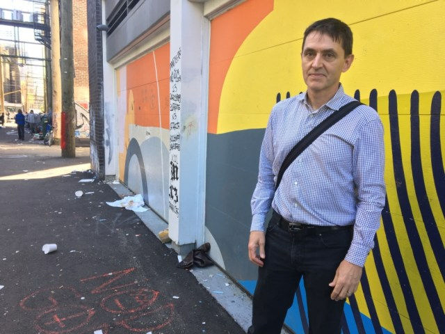 A man stands in a colorful alley