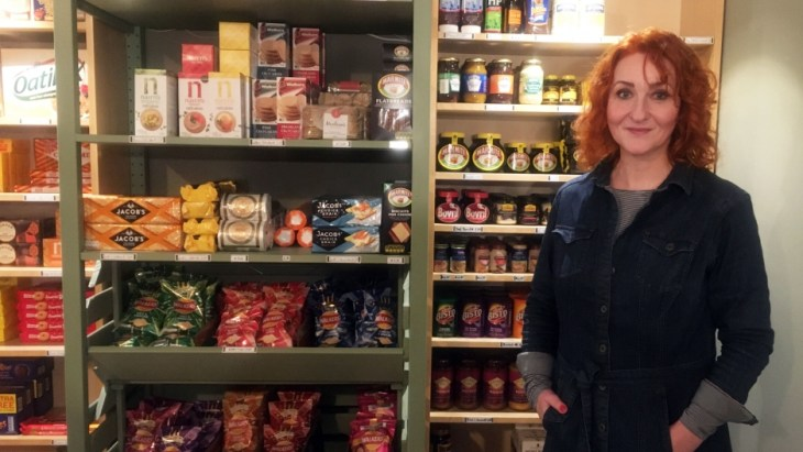 A woman stands by stocked shelfs in a shop