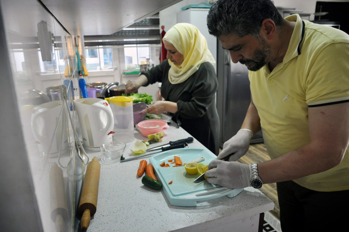 A man and woman prepare food together in a kitchen
