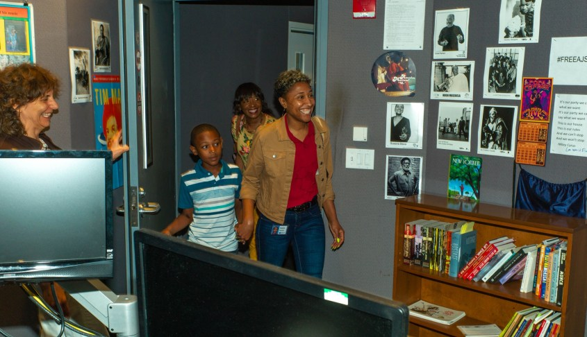 A woman smiles as she walks through a door, with other family members behind her