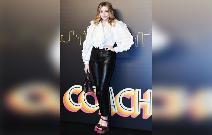 Chloe Grace Moretz in a white top and black pants.