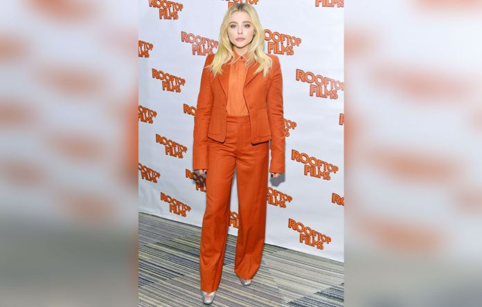 Chloe Grace Moretz in a red outfit on the red carpet.