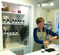 Rebecca Kroll, front desk coordinator of The Still Point Mind and Body, a Wellness Spa in Takoma Park, MD, dispenses essential oil from a burette.