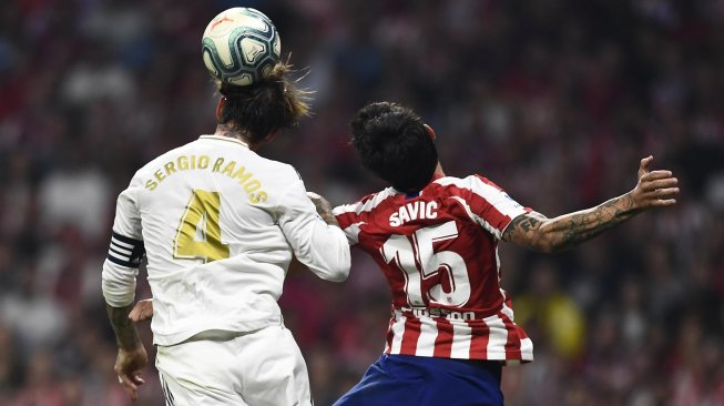 Real Madrid defender Sergio Ramos and Atletico Madrid defender Stefan Savic jump to get the ball during the Spanish league football match between Atletico Madrid and Real Madrid at the Wanda Metropolitano stadium, Madrid, Spain, Sunday (29/9) early morning WIB. [OSCAR DEL POZO / AFP]
