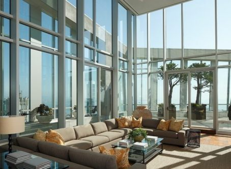 spacious living room area with big gray sectional sofa and chic floral cushions under high ceiling with glass wall