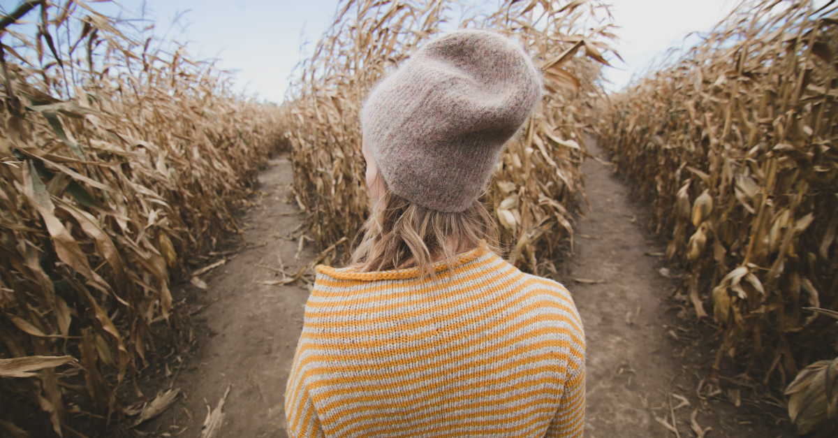 young woman standing at crossroad in a cornfield, trying to make a decision