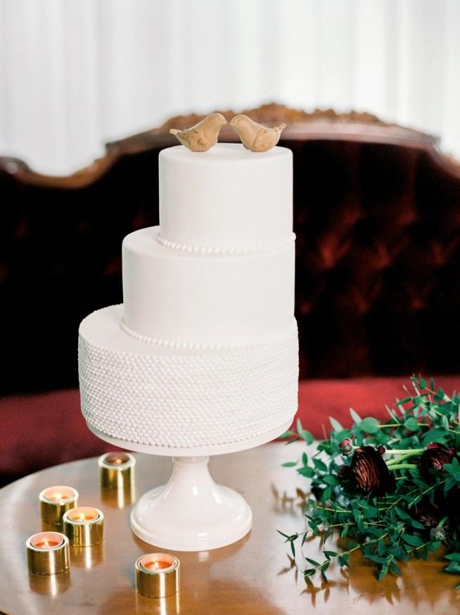 Vit bröllopstårta från Cake Art med fåglar på toppen.