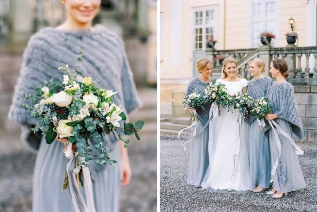 Bruden med täror utanför slottet. Tärnorna i grå klänningar med vackra gråblå ponchos