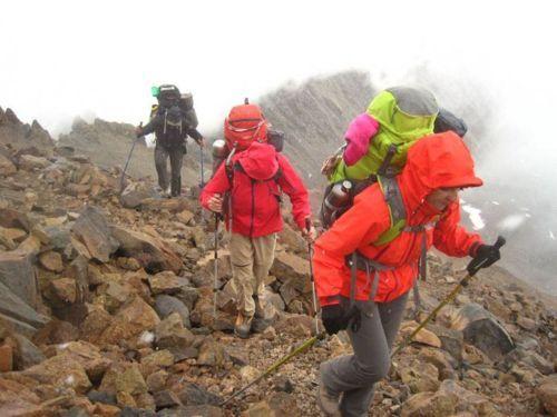 Tres personas haciendo trekking hacia el Cerro Marmolejo.
