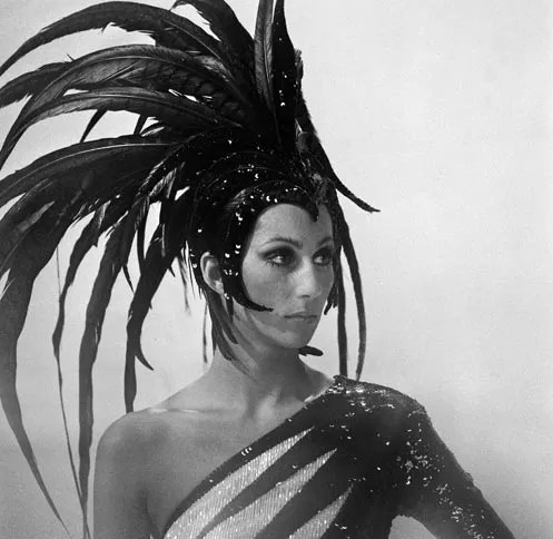 Cher in Bob Mackie one-shouldered beaded dress and feathered headdress, c. 1973