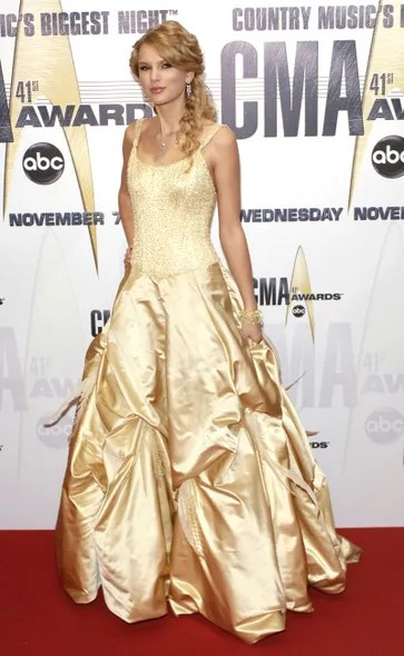"""Aiming for a glamorous look for 2007's Country Music Association Awards, Swift's southern-gal gown didn't so much say, """"Belle of the ball,"""" as """"Belle from *Beauty and the Beast.*"""" Still, her elegant hair and jewelry were making definite strides."""
