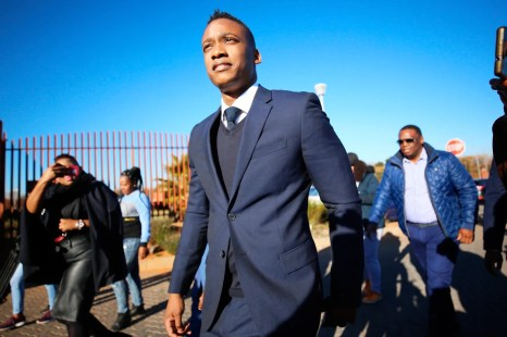 Duduzane Zuma walking in a blue suit.