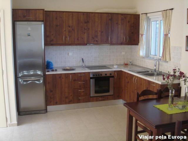 Cozinha equipada com geladeira, fogão e outros utensílios.