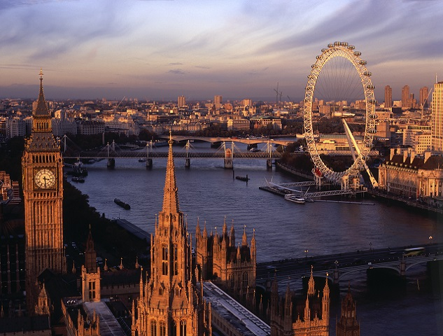 View from the top of the Victoria Tower, the lesser known of the two towers of the Houses of Parliament, towards Big Ben, the River Thames and the London Eye Millennium Wheel, Westminster and the cityscape to the east. Dusk. Sunset. Britain 100.