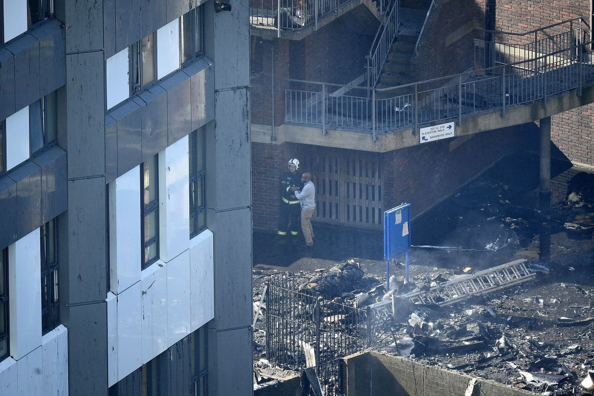 LONDON, ENGLAND - JUNE 14: A man speaks to a fire fighter after a huge fire engulfed the 24 sage Grenfell Tower in Latimer Road, West London in the early hours of this morning on June 14, 2017 in London, England.  The Mayor of London, Sadiq Khan, has declared the fire a major incident as more than 200 firefighters are still tackling the blaze, while at least 50 people are receiving hospital treatment.  (Photo by Leon Neal/Getty Images)