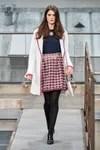Modelo con falda de tweed, blusa azul y abrigo blanco de Chanel