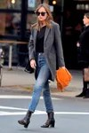Dakota Johnson displays a street style composed by skinny jeans, ankle boots and a sack