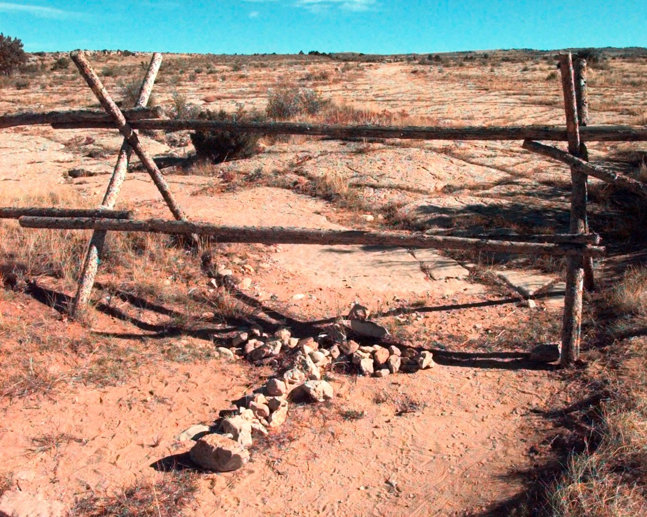 FILE - A cross made of stones rests below the fence in Laramie, Wyo., where a year earlier, University of Wyoming student Matthew Shepard was tied and pistol whipped into a coma, Oct. 9, 1999.