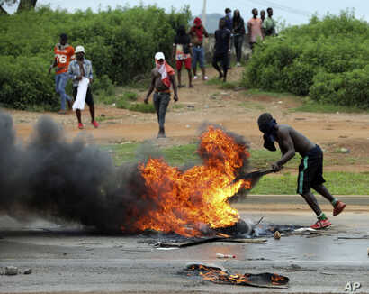 A protester sets a fire on the road opposite Shoprite in Abuja, Nigeria, Sept. 4, 2019. South African-owned businesses operating in Nigeria are being targeted with violence in retaliation for attacks carried out against Africans working in South Africa.