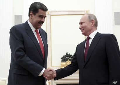 Russian President Vladimir Putin, right, shakes hands with Venezuela's President Nicolas Maduro during their meeting in the Kremlin in Moscow, Russia, Sept. 25, 2019.