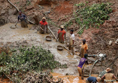 FILE - Men work at Makala gold mine camp near the town of Mongbwalu in Ituri province, eastern Democratic Republic of Congo, April 7, 2018.