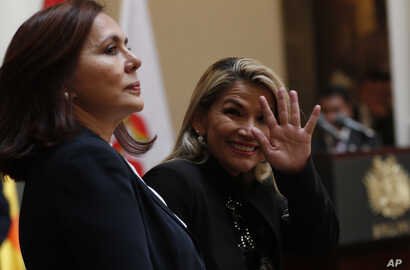 Accompanied by Bolivia's Foreign Minister Karen Longaric, interim President Jeanine Anez waves to journalists during a protocol
