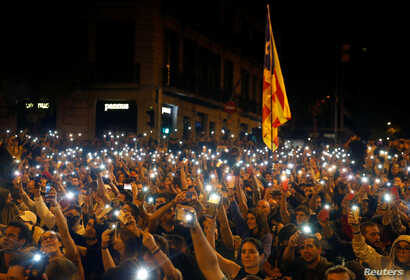 FILE - Demonstrators light their mobile phones during a protest in Barcelona, Spain, Oct. 19, 2019.