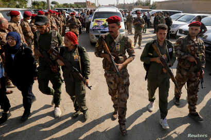 Fighters of Syrian Democratic Forces (SDF) take part in the funeral procession of Kurdish fighters who were killed during…