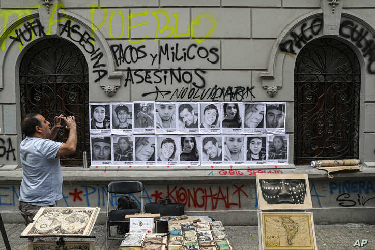 A man takes a photo of portraits of people that have died during anti-government protests in Santiago, Chile, Friday, Nov. 1,