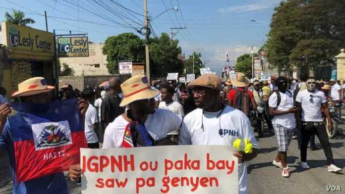 Police protesters hold a banner that says IGPNH (inspector general of police) you cant give what you dont have, Nov 17, 2019, Port au Prince. (Photo: M. Vilme/VOA)