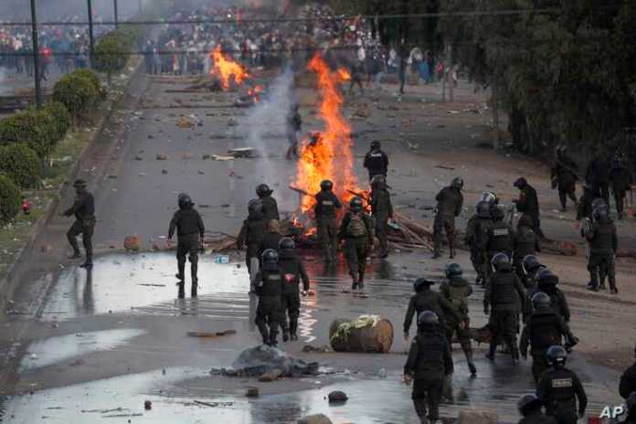 Police dismantle a barricade constructed by supporters of former President Evo Morales, on the outskirts of Cochabamba, Bolivia, Nov. 16, 2019.