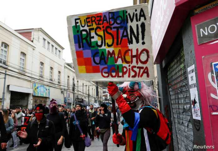 """A demonstrator holds a placard that reads """"Bolivia Force, Resist, Camacho coup"""" during a protest against Chile's government in Valparaiso, Chile, Nov. 12, 2019."""