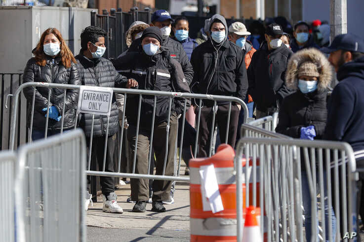 Patients wearing face masks and personal protective equipment wait on line for COVID-19 testing outside Elmhurst Hospital