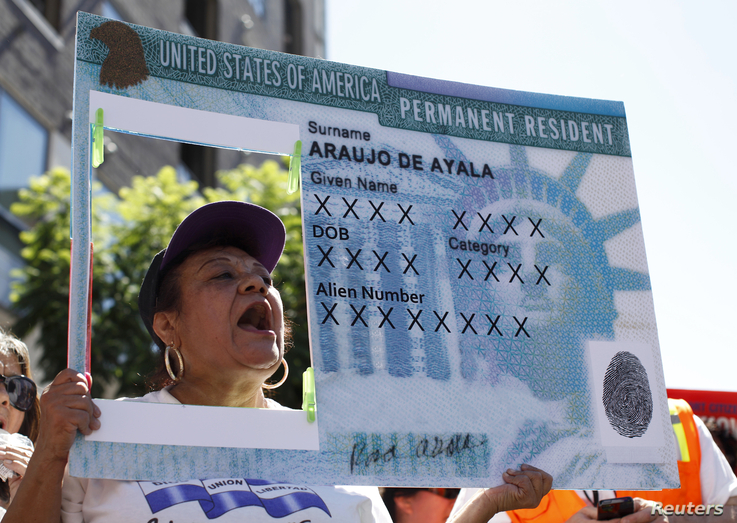 FILE - A woman holds an enlarged replica of a green card during a rally to demand immigration reform, Los Angeles, California, Oct. 5, 2013.