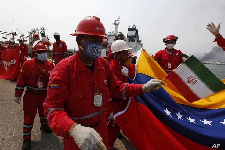 A Venezuelan oil worker holds a small Iranian flag during a ceremony marking the arrival of Iranian oil tanker Fortune at the El Palito refinery near Puerto Cabello, Venezuela, May 25, 2020.