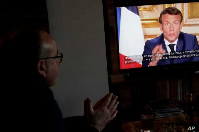 Giuseppe Fonsino, listens to the speech of French President Emmanuel Macron on television, in Ville d'Avray, near Paris, Monday April…