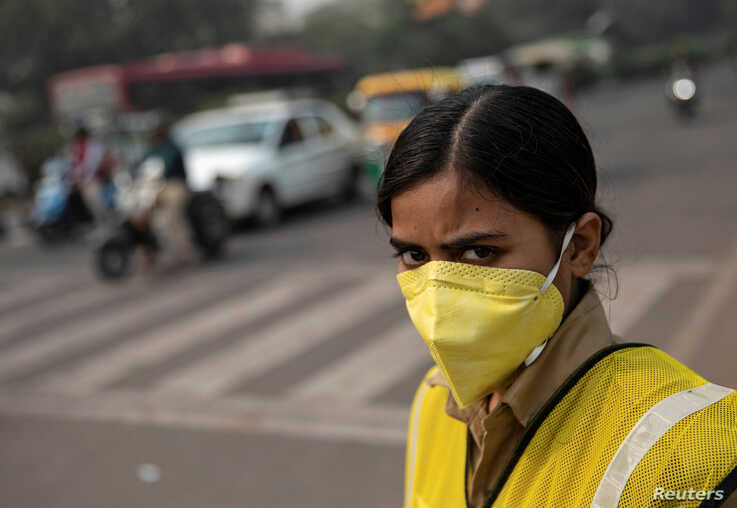 A policewoman wears a mask to protect herself from air pollution at a junction during restrictions on private vehicles based on