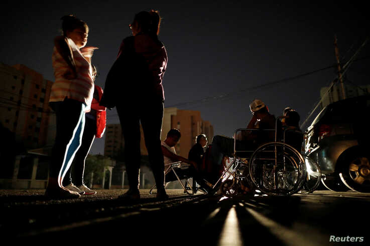 Patients with kidney disease and their relatives wait on the street for the return of electricity, in front of a dialysis