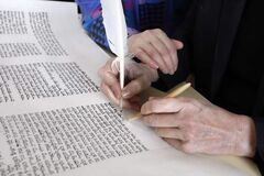 Irma Penn writes on Torah scroll as Ruth Livingston places her hand on Penn's hand.