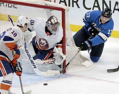 Adam Lowry of Winnipeg Jets tries to make a turn on Thursday against New York Islanders Goalie Semyon Varlamov at Bell MTS Place.