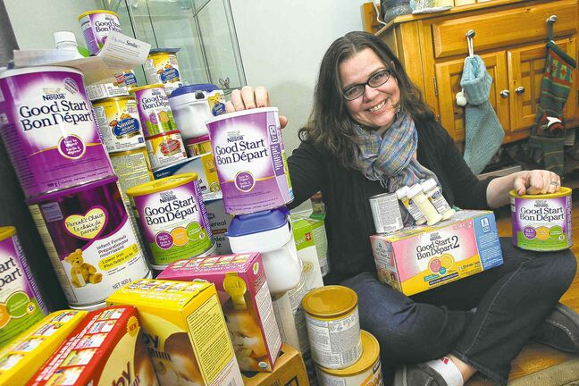 A woman sits next to many boxes and tins of baby formula