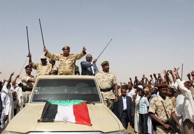 Sudanese President Omar al-Bashir, center, waves from the back of a truck during a visit to North Kordofan, Sudan, Thursday, April 19, 2012. The Arab League said Thursday it would hold an emergency meeting over the increasing violence between Sudan and South Sudan. Sudan President Omar al-Bashir on Wednesday threatened to topple the South Sudan government after accusing the south of trying to take down his Khartoum-based government. Al-Bashir continued his hardline rhetoric on Thursday in an address to a