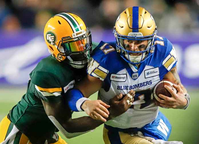 Chris Streveler, quarterback of Winnipeg Blue Bombers, runs to the right as Larry Dean of Edmonton Eskimos tries to tackle him during the second-time CFL football action in Edmonton, Friday.