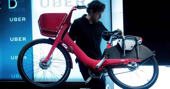 Man removing a JUMP bike off stage during an uber event
