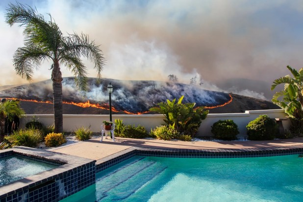 Gadgets: Fire advances on a hilltop near an aquamarine pool in this image Kevin Cooley captured during the Woolsey Fire in 2018.nbsp