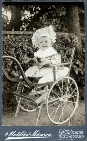 Glad men okänd grabb i barnvagn från sekelskiftet 1900.