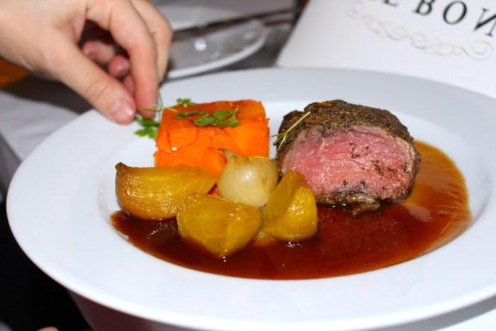 Huvudrätten serveras. Kryddstarkt ryggbiff med morotsterrin, saltbakad gulbeta, rökt lök och potatispuré samt rödvinssky.