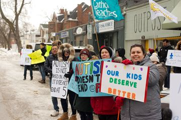 Protesters line Woolwich Street, in front of MPP Mike Schreiner's office, to protest the provincial government's changes to autism funding in February. On Thursday, KidsAbility announced it would be laying off half of its workers who help kids with autism.