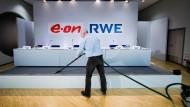 Ein Mann saugt vor einer gemeinsamen Pressekonferenz von RWE und E.ON das Podium (Archivbild).